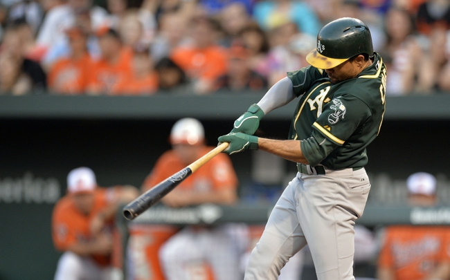 Jun 7, 2014; Baltimore, MD, USA; Oakland Athletics center fielder Coco Crisp (4) hits a solo home run in the third inning against the Baltimore Orioles at Oriole Park at Camden Yards. Mandatory Credit: Joy R. Absalon-USA TODAY Sports