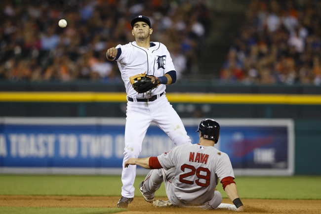 Jun 7, 2014; Detroit, MI, USA; Detroit Tigers shortstop Eugenio Suarez (30) makes a throw to first in an attempted double play as Boston Red Sox left fielder Daniel Nava (29) slides into second in the eighth inning at Comerica Park. Mandatory Credit: Rick Osentoski-USA TODAY Sports