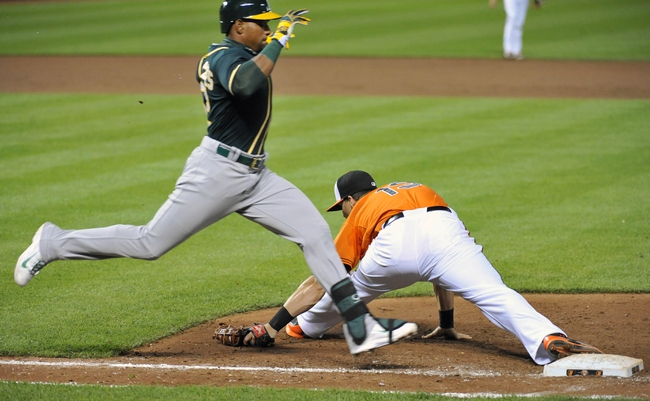 Jun 7, 2014; Baltimore, MD, USA; Baltimore Orioles first baseman Chris Davis (19) stretches to make the play as Oakland Athletics left fielder Yoenis Cespedes (not shown) grounds out in the ninth inning at Oriole Park at Camden Yards. The Orioles defeated the Athletics 6-3. Mandatory Credit: Joy R. Absalon-USA TODAY Sports