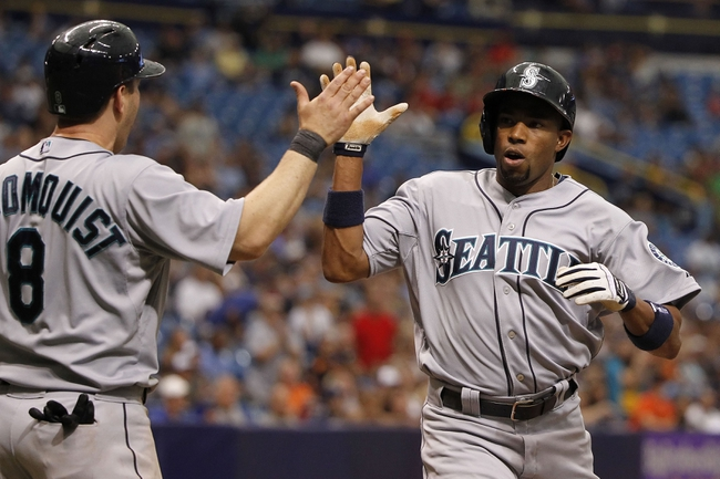 Jun 8, 2014; St. Petersburg, FL, USA; Seattle Mariners left fielder Endy Chavez (9) celebrates with shortstop Willie Bloomquist (8) after both scoring against the Tampa Bay Rays at Tropicana Field. The Mariners won 5-0. Mandatory Credit: Kim Klement-USA TODAY Sports