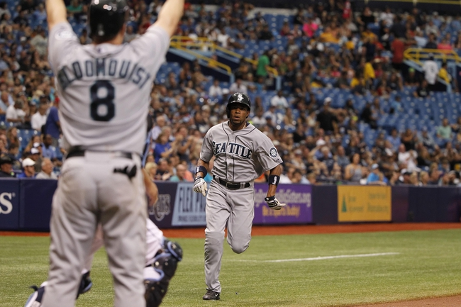 Jun 8, 2014; St. Petersburg, FL, USA; Seattle Mariners left fielder Endy Chavez (9) runs home as shortstop Willie Bloomquist (8) celebrates after he scored against the Tampa Bay Rays during the ninth inning at Tropicana Field. The Mariners won 5-0. Mandatory Credit: Kim Klement-USA TODAY Sports