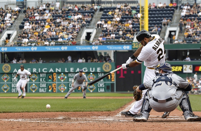Jun 8, 2014; Pittsburgh, PA, USA; Pittsburgh Pirates third baseman Pedro Alvarez (24) hits an infield single against the Milwaukee Brewers during the seventh inning at PNC Park. The Brewers won 1-0. Mandatory Credit: Charles LeClaire-USA TODAY Sports