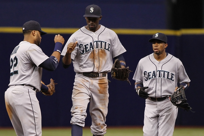 Jun 8, 2014; St. Petersburg, FL, USA; Seattle Mariners center fielder James Jones (99) celebrates with second baseman Robinson Cano (22) after defeating the Tampa Bay Rays 5-0 at Tropicana Field. Mandatory Credit: Kim Klement-USA TODAY Sports