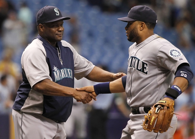 Jun 8, 2014; St. Petersburg, FL, USA; Seattle Mariners manager Lloyd McClendon (23) celebrates with second baseman Robinson Cano (22) after defeating the Tampa Bay Rays 5-0 at Tropicana Field. Mandatory Credit: Kim Klement-USA TODAY Sports