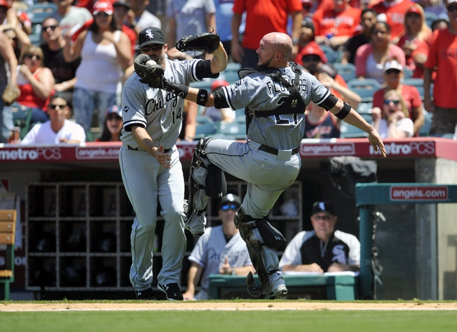 June 8, 2014; Anaheim, CA, USA; Chicago White Sox catcher Tyler Flowers (21) nearly collides with first baseman Paul Konerko (14) as he catches a foul ball in the fifth inning against the Los Angeles Angels at Angel Stadium of Anaheim. Mandatory Credit: Gary A. Vasquez-USA TODAY Sports