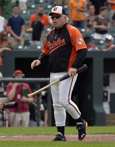 Jun 8, 2014; Baltimore, MD, USA; Baltimore Orioles manager Buck Showalter (26) walks off the field with Manny Machado's (not shown) bat after Machado was ejected in the eighth inning against the Oakland Athletics at Oriole Park at Camden Yards. The Athletics won 11-1. Mandatory Credit: Joy R. Absalon-USA TODAY Sports