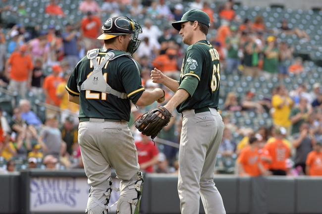 Jun 8, 2014; Baltimore, MD, USA; Oakland Athletics catcher Stephen Vogt (21) congratulates pitcher Dan Otero (61) after a game against the Baltimore Orioles at Oriole Park at Camden Yards. The Athletics defeated the Orioles 11-1. Mandatory Credit: Joy R. Absalon-USA TODAY Sports