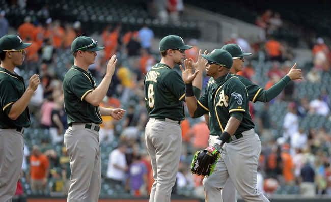 Jun 8, 2014; Baltimore, MD, USA; Oakland Athletics teammates Jed Lowrie (left) and Yoenis Cespedes (right) high-five after a game against the Baltimore Orioles at Oriole Park at Camden Yards. The Athletics defeated the Orioles 11-1. Mandatory Credit: Joy R. Absalon-USA TODAY Sports