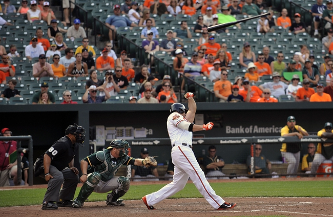 Jun 8, 2014; Baltimore, MD, USA; Baltimore Orioles first baseman Chris Davis (19) loses his bat into the stands during the eighth inning against the Oakland Athletics at Oriole Park at Camden Yards. The Athletics defeated the Orioles 11-1. Mandatory Credit: Joy R. Absalon-USA TODAY Sports