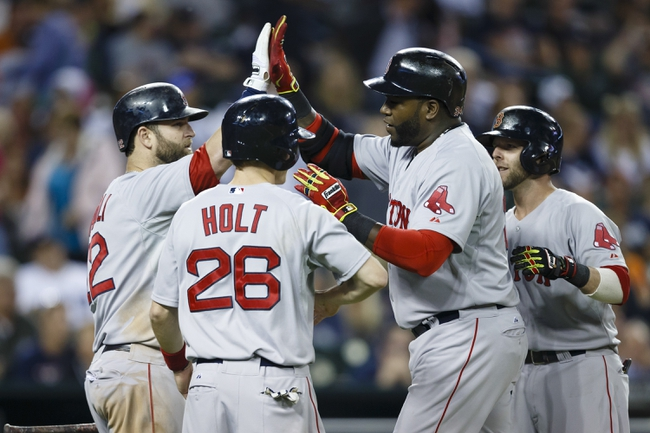 Jun 8, 2014; Detroit, MI, USA; Boston Red Sox designated hitter David Ortiz (center) receives congratulations from first baseman Mike Napoli (left) and left fielder Brock Holt (26) and second baseman Dustin Pedroia (right) after he hits a three run home run in the ninth inning against the Detroit Tigers at Comerica Park. Boston won 5-3. Mandatory Credit: Rick Osentoski-USA TODAY Sports