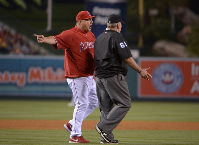 Jun 9, 2014; Anaheim, CA, USA; Los Angeles Angels manager Mike Scioscia (left) reacts after being ejected by first base umpire Bob Davidson (61) in the fifth inning against the Oakland Athletics at Angel Stadium of Anaheim. Mandatory Credit: Kirby Lee-USA TODAY Sports