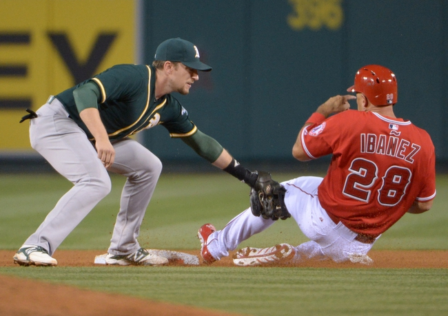Jun 9, 2014; Anaheim, CA, USA; Oakland Athletics second baseman Jed Lowrie tags out Los Angeles Angels designated hitter Raul Ibanez (28) on a stolen base attempt in the fourth inning at Angel Stadium of Anaheim. Mandatory Credit: Kirby Lee-USA TODAY Sports