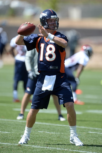 Jun 10, 2014; Denver, CO, USA; Denver Broncos quarterback Peyton Manning (18) prepares to pass during mini camp drills at the Broncos practice facility. Mandatory Credit: Ron Chenoy-USA TODAY Sports