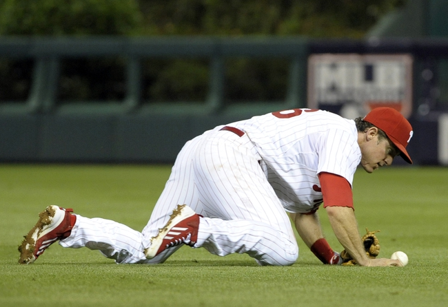 Jun 10, 2014; Philadelphia, PA, USA; Philadelphia Phillies second baseman Chase Utley (26) knocks down the baseball in the ninth inning against the San Diego Padres at Citizens Bank Park. Phillies defeated the Padres, 5-2. Mandatory Credit: Eric Hartline-USA TODAY Sports
