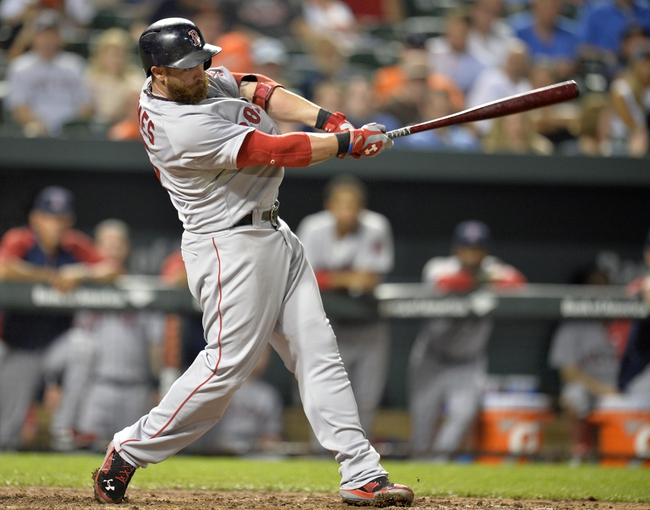 Jun 10, 2014; Baltimore, MD, USA; Boston Red Sox pinch hitter Jonny Gomes (5) singles in the eighth inning against the Baltimore Orioles at Oriole Park at Camden Yards. The Red Sox defeated the Orioles 1-0. Mandatory Credit: Joy R. Absalon-USA TODAY Sports