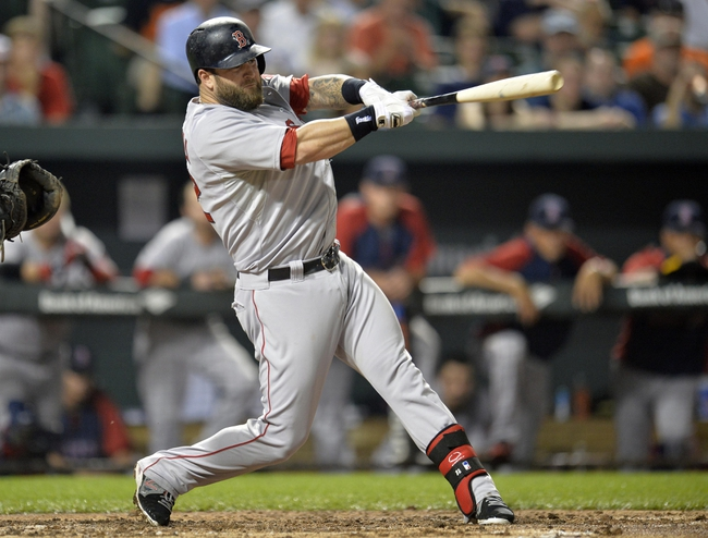 Jun 10, 2014; Baltimore, MD, USA; Boston Red Sox first baseman Mike Napoli (12) hits a one-run rbi single in the third inning against the Baltimore Orioles at Oriole Park at Camden Yards. The Red Sox defeated the Orioles 1-0. Mandatory Credit: Joy R. Absalon-USA TODAY Sports