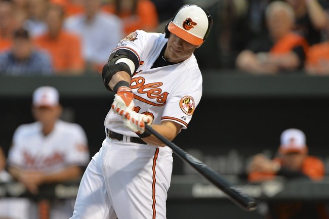 Jun 11, 2014; Baltimore, MD, USA;  Baltimore Orioles first baseman Chris Davis (19) hits a two run home run in the first inning against the Boston Red Sox at Oriole Park at Camden Yards. Mandatory Credit: Tommy Gilligan-USA TODAY Sports