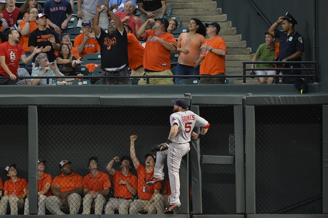 Jun 11, 2014; Baltimore, MD, USA;  A fan catches Baltimore Orioles first baseman Chris Davis (19) (not pictured) over Boston Red Sox left fielder Jonny Gomes (5) during the first inning at Oriole Park at Camden Yards. Mandatory Credit: Tommy Gilligan-USA TODAY Sports