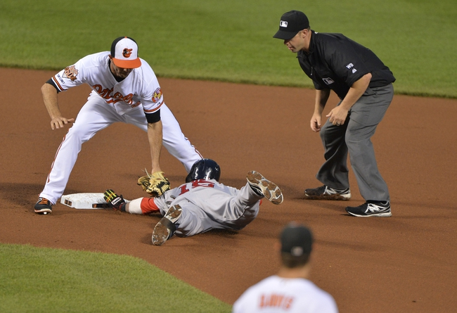 Jun 11, 2014; Baltimore, MD, USA;  Boston Red Sox second baseman Dustin Pedroia (15) is tagged out at second by Baltimore Orioles shortstop J.J. Hardy (2) as he attempts to stretch for extra bases during the fourth inning  at Oriole Park at Camden Yards. Mandatory Credit: Tommy Gilligan-USA TODAY Sports