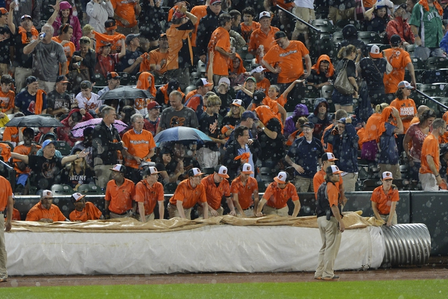 Jun 11, 2014; Baltimore, MD, USA; The grounds crew prepares to roll out the the field tarp as the during the seventh inning of the game between the Boston Red Sox and Baltimore Orioles  at Oriole Park at Camden Yards. Mandatory Credit: Tommy Gilligan-USA TODAY Sports