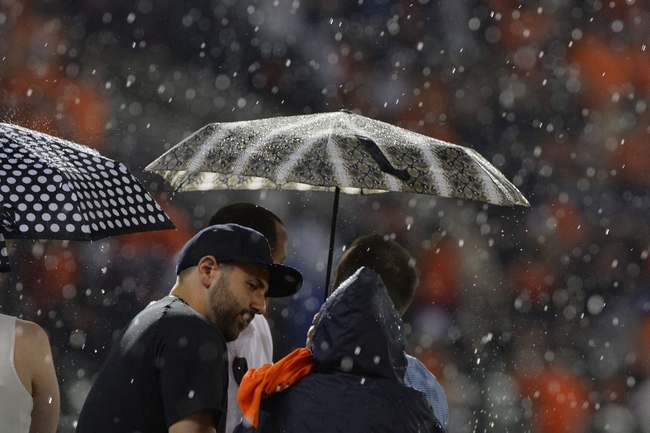 Jun 11, 2014; Baltimore, MD, USA;  Fans take cover under umbrellas as the rain comes down during seventh inning of the game between the Boston Red Sox and Baltimore Orioles the at Oriole Park at Camden Yards. Mandatory Credit: Tommy Gilligan-USA TODAY Sports