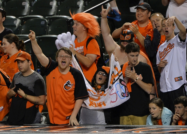 Jun 11, 2014; Baltimore, MD, USA;  Baltimore Orioles fans begin to celebrate with two out in the top of the  ninth inning against the Boston Red Sox  after at Oriole Park at Camden Yards. Baltimore Orioles defeated Boston Red Sox 6-0. Mandatory Credit: Tommy Gilligan-USA TODAY Sports