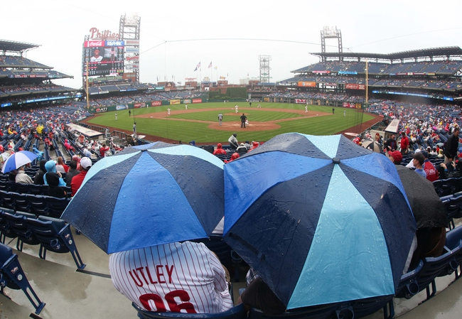 Jun 12, 2014; Philadelphia, PA, USA; Fans sit under umbrellas in the rain as the Philadelphia Phillies and San Diego Padres play during the fourth inning of a game at Citizens Bank Park. Mandatory Credit: Bill Streicher-USA TODAY Sports