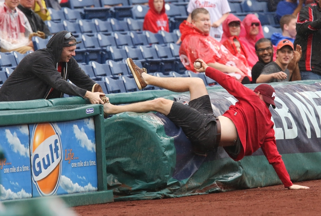 Jun 12, 2014; Philadelphia, PA, USA; While going for a foul ball a fan falls over the field railing as his friend grabs his foot in a game between the Philadelphia Phillies and San Diego Padres at Citizens Bank Park. Mandatory Credit: Bill Streicher-USA TODAY Sports