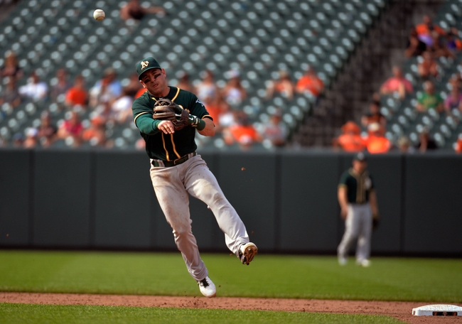 Jun 8, 2014; Baltimore, MD, USA; Oakland Athletics shortstop Nick Punto (1) throws over to first base in the ninth inning against the Baltimore Orioles at Oriole Park at Camden Yards. The Athletics defeated the Orioles 11-1. Mandatory Credit: Joy R. Absalon-USA TODAY Sports