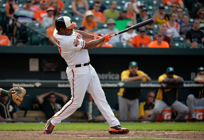 Jun 8, 2014; Baltimore, MD, USA; Baltimore Orioles pinch hitter Delmon Young (27) singles in the eighth inning against the Oakland Athletics at Oriole Park at Camden Yards. The Athletics defeated the Orioles 11-1. Mandatory Credit: Joy R. Absalon-USA TODAY Sports