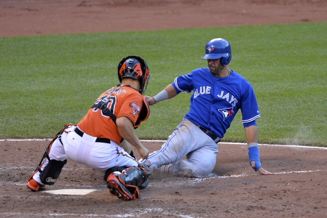 Jun 14, 2014; Baltimore, MD, USA;  Baltimore Orioles catcher Nick Hundley (40) tags out Toronto Blue Jays right fielder Jose Bautista (19) at home during the eighth inning at Oriole Park at Camden Yards. Baltimore Orioles defeats the Toronto Blue Jays 3-2. Mandatory Credit: Tommy Gilligan-USA TODAY Sports