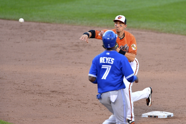 Jun 14, 2014; Baltimore, MD, USA; Baltimore Orioles third baseman Ryan Flaherty (3) turns a game ending double play in the ninth inning against the Toronto Blue Jays  at Oriole Park at Camden Yards. Baltimore Orioles defeats the Toronto Blue Jays 3-2. Mandatory Credit: Tommy Gilligan-USA TODAY Sports