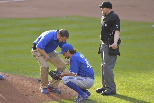 Jun 14, 2014; Baltimore, MD, USA;  Toronto Blue Jays medical staff checks on  starting pitcher R.A. Dickey (43) prior to being removed from the game in the seventh inning against the Baltimore Orioles at Oriole Park at Camden Yards. Baltimore Orioles defeats the Toronto Blue Jays 3-2. Mandatory Credit: Tommy Gilligan-USA TODAY Sports