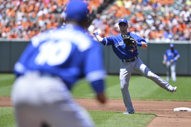 Jun 15, 2014; Baltimore, MD, USA; Toronto Blue Jays second baseman Steve Tolleson (18) throws to first baseman Edwin Encarnacion (10)  for the force out during the first inning against the Baltimore Orioles at Oriole Park at Camden Yards. Mandatory Credit: Tommy Gilligan-USA TODAY Sports