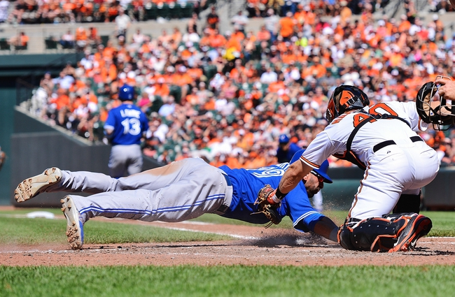 Jun 15, 2014; Baltimore, MD, USA;  Toronto Blue Jays right fielder Jose Bautista (19) is tagged out at the plate by Baltimore Orioles catcher Nick Hundley (40) during the eighth inning at Oriole Park at Camden Yards. Toronto Blue Jays defeat the Baltimore Orioles 5-2. Mandatory Credit: Tommy Gilligan-USA TODAY Sports