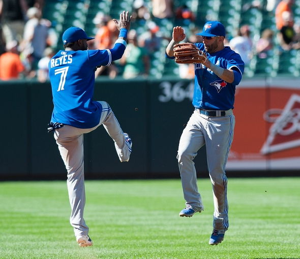 Jun 15, 2014; Baltimore, MD, USA; Toronto Blue Jays shortstop Jose Reyes (7) and  right fielder Jose Bautista (19)   celebrate after defeating the Baltimore Orioles 5-2 at Oriole Park at Camden Yards. Mandatory Credit: Tommy Gilligan-USA TODAY Sports
