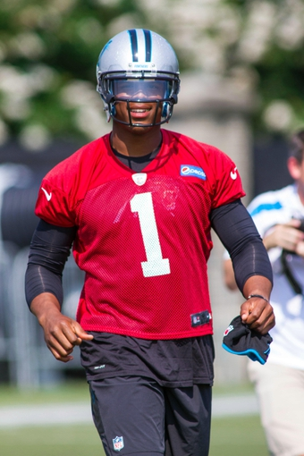 Jun 17, 2014; Charlotte, NC, USA; Carolina Panthers quarterback Cam Newton walks on the field prior to the start of the minicamp held at the Carolina Panthers practice facility. Mandatory Credit: Jeremy Brevard-USA TODAY Sports