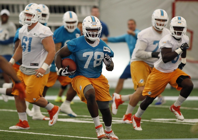 Jun 17, 2014; Davie, FL, USA; Miami Dolphins defensive end Terrence Fede runs with the ball after intercepting a pass during mini-camp at Miami Dolphins Training Facility.  Mandatory Credit: Robert Mayer-USA TODAY Sports