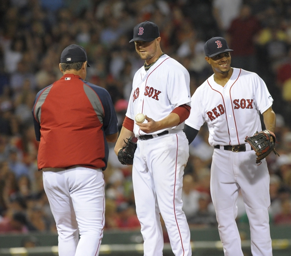 Jun 17, 2014; Boston, MA, USA; Boston Red Sox starting pitcher Jon Lester (31) hands the ball to manager John Farrell (53) while being congratulated by third baseman Xander Bogaerts (2) during the seventh inning against the Minnesota Twins at Fenway Park. Mandatory Credit: Bob DeChiara-USA TODAY Sports