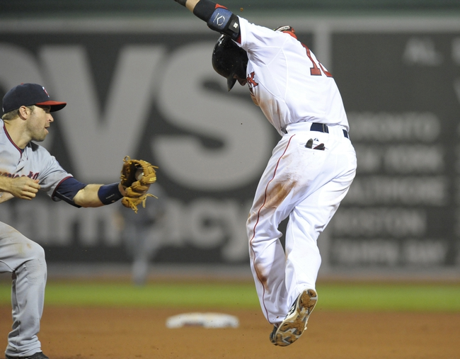 Jun 17, 2014; Boston, MA, USA; Boston Red Sox second baseman Dustin Pedroia (15) avoids the tag of Minnesota Twins second baseman Brian Dozier (2) but is called out for running out of the base path during the eighth inning at Fenway Park. Mandatory Credit: Bob DeChiara-USA TODAY Sports