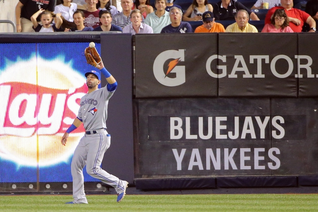 Jun 17, 2014; Bronx, NY, USA;  Toronto Blue Jays right fielder Jose Bautista (19) fields a ball during the fourth inning against the New York Yankees at Yankee Stadium. New York Yankees won 3-1. Mandatory Credit: Anthony Gruppuso-USA TODAY Sports
