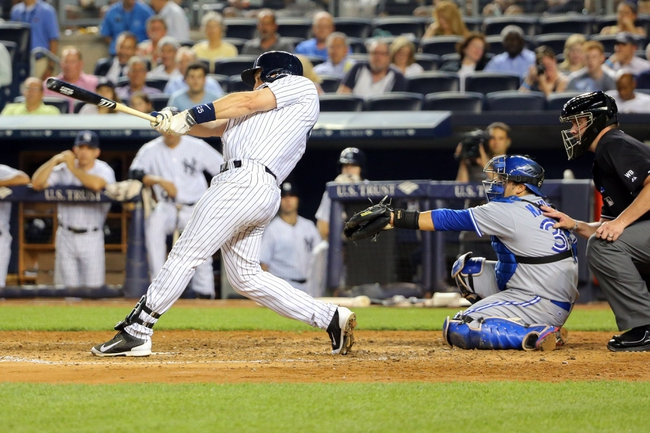 Jun 17, 2014; Bronx, NY, USA;  New York Yankees first baseman Mark Teixeira (25) singles to center scoring shortstop Derek Jeter (2) during the fifth inning against the Toronto Blue Jays at Yankee Stadium. New York Yankees won 3-1. Mandatory Credit: Anthony Gruppuso-USA TODAY Sports