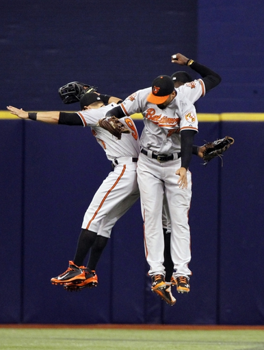 Jun 17, 2014; St. Petersburg, FL, USA; Baltimore Orioles left fielder David Lough (9), center fielder Adam Jones (10) and right fielder Nick Markakis (21) celebrate after they beat the Tampa Bay Rays at Tropicana Field. Baltimore Orioles defeated the Tampa Bay Rays 7-5. Mandatory Credit: Kim Klement-USA TODAY Sports