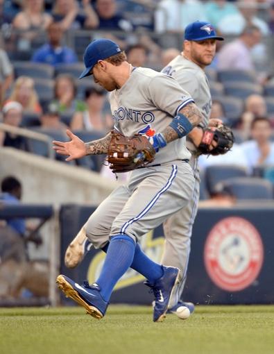 Jun 18, 2014; Bronx, NY, USA; Toronto Blue Jays third baseman Brett Lawrie commits a fielding error on a ball hit by New York Yankees shortstop Derek Jeter (not pictured) during the MLB baseball game at Yankee Stadium. Mandatory Credit: Robert Deutsch-USA TODAY Sports