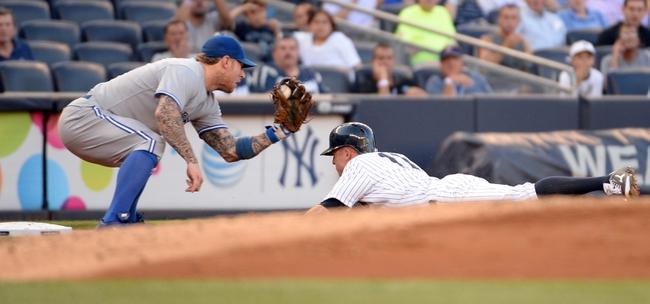 Jun 18, 2014; Bronx, NY, USA; New York Yankees left fielder Brett Gardner (11) slides into third base ahead of the throw to Toronto Blue Jays third baseman Brett Lawrie (left) during the MLB baseball game at Yankee Stadium. Mandatory Credit: Robert Deutsch-USA TODAY Sports