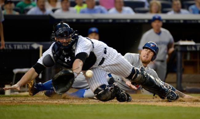 Jun 18, 2014; Bronx, NY, USA; Toronto Blue Jays third baseman Brett Lawrie (rear) scores a run as the ball gets away from New York Yankees catcher Brian McCann (front) in the 4th inning during the MLB baseball game at Yankee Stadium. Mandatory Credit: Robert Deutsch-USA TODAY Sports