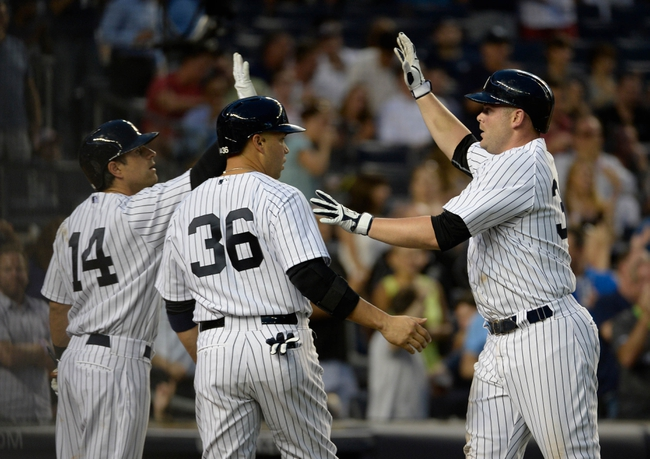 Jun 18, 2014; Bronx, NY, USA; New York Yankees catcher Brian McCann (right) celebrates with teammates Carlos Beltran (36) ad Brian Roberts (14) after hitting a two-run home run in the 4th inning against the Toronto Blue Jays during the MLB baseball game at Yankee Stadium. Mandatory Credit: Robert Deutsch-USA TODAY Sports