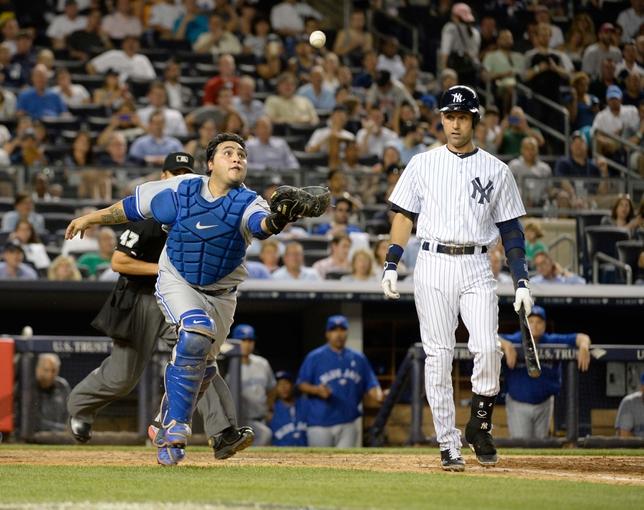 Jun 18, 2014; Bronx, NY, USA; New York Yankees shortstop Derek Jeter (right) pops out on a bunt attempt to Toronto Blue Jays catcher Dioner Navarro (left) during the MLB baseball game at Yankee Stadium. Mandatory Credit: Robert Deutsch-USA TODAY Sports