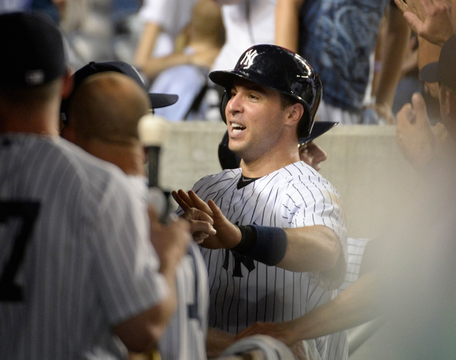 Jun 18, 2014; Bronx, NY, USA; New York Yankees first baseman Mark Teixeira is congratulated by teammates in the dugout after scoring a run against the Toronto Blue Jays in the 7th inning during the MLB baseball game at Yankee Stadium. Mandatory Credit: Robert Deutsch-USA TODAY Sports