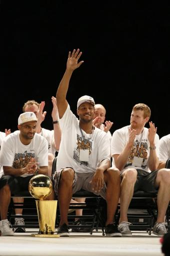 Jun 18, 2014; San Antonio, TX, USA; San Antonio Spurs forward Boris Diaw (middle) waves to the crowd during NBA championship celebrations at Alamodome. Mandatory Credit: Soobum Im-USA TODAY Sports